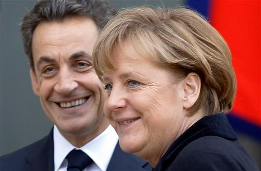 French President Nicolas Sarkozy, left, smiles as he greets German Chancellor Angela Merkel prior to their meeting at the Elysee Palace in Paris, Monday Dec. 5, 2011.