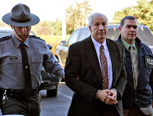 This Nov. 5, 2011 file photo shows former Penn State football defensive coordinator Jerry Sandusky, center, wearing handcuffs. (AP Photo/The Patriot-News, Andy Colwell, File)