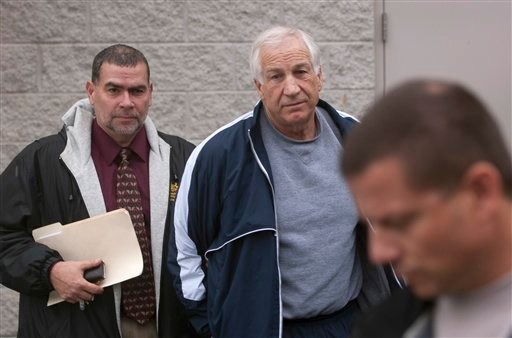 Former Penn State assistant football coach Jerry Sandusky, center, leaves the office of Centre County District Justice Daniel A. Hoffman under escort by Pennsylvania State Police and Attorney General's Office officials in Bellefonte, Pa., on December 7.