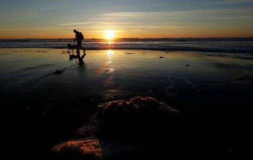 A man walks his dog at Ocean Beach as the sun sets in San Francisco, Tuesday, Feb. 27, 2018. Forecasters said the next weather system will arrive in Northern California on Wednesday, and reach the south by Thursday, bringing much more precipitation. (AP P