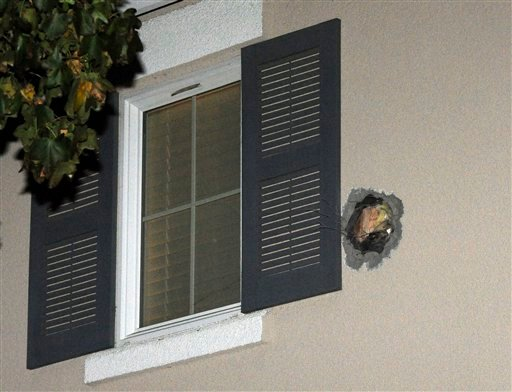 The exit hole from a misfired cannonball is seen in the second story wall after it traveled through a Dublin, Calif., home on Cassata Place on Tuesday, Dec. 6, 2011.