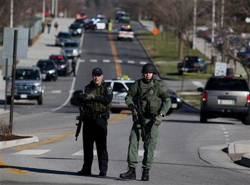 Police officers block a road on the Virginia Tech campus in Blacksburg, Va., after a gunman killed a police officer and another person Thursday, Dec. 8, 2011.