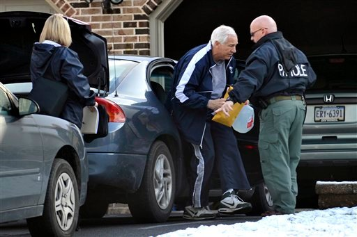 Former Penn State football coach Jerry Sandusky gets out of a car in front of his State College, Pa., home on Thursday, Dec. 8, 2011.
