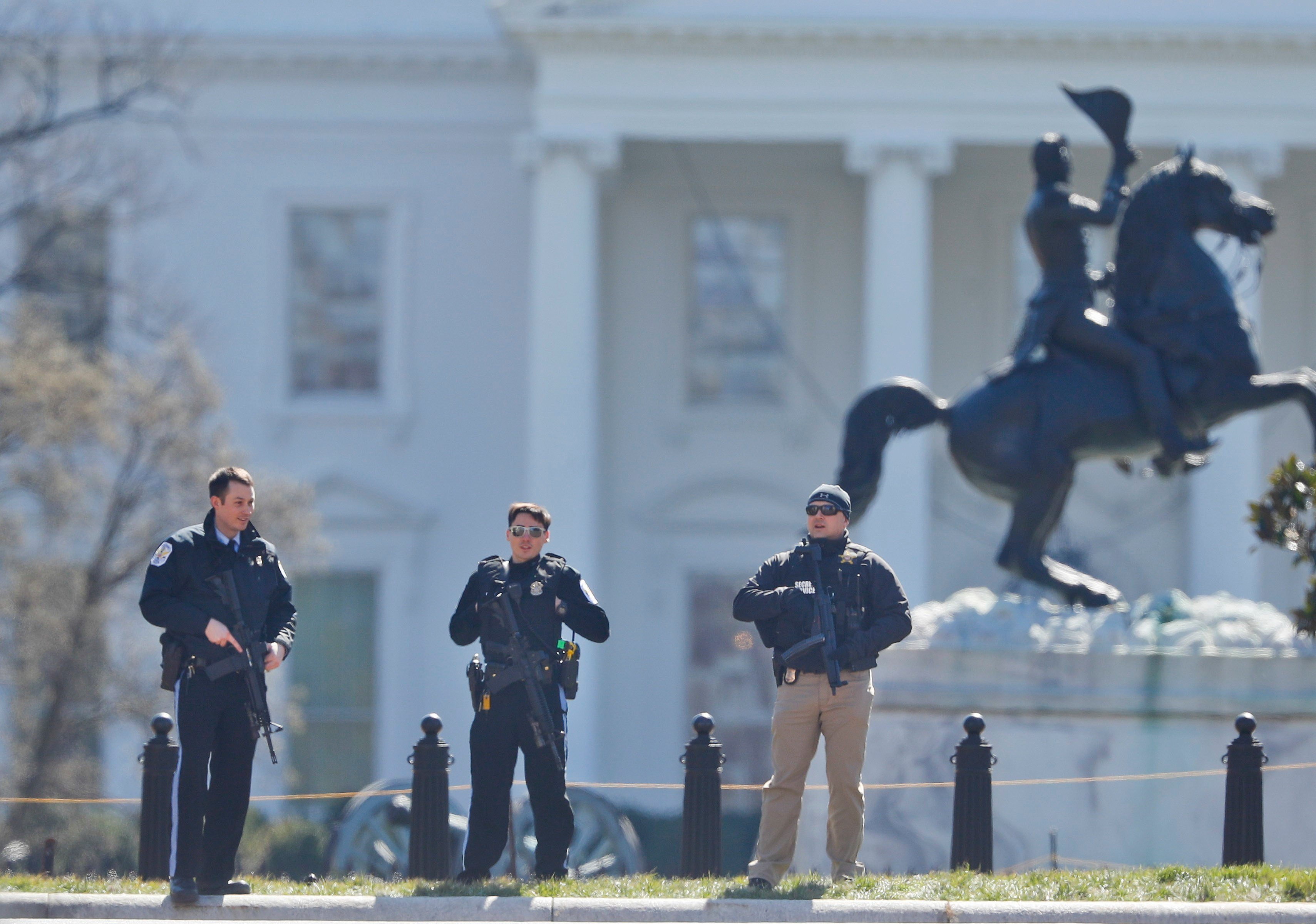 Law enforcement officers stand at the entrance to Lafayette Park across from the White House in Washington, after they area was closed to pedestrian traffic. A man apparently shot himself along the north fence of the White House. AP Photo/Pablo Martinez