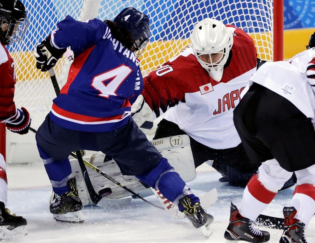 Goalie Akane Konishi (30), of Japan, blocks a shot by North Korea's Kim Un Hyang (4), during the third period of a women's hockey game at the 2018 Winter Olympics in Gangneung, South Korea, Wednesday, Feb. 14, 2018. (AP Photo/Frank Franklin II)