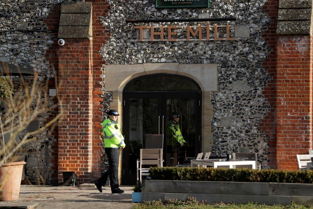 A police community support officer stands inside a cordon outside The Mill pub in Salisbury, England.