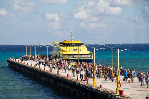 Tourists and passengers disembark from a ferry on to the wharf on Playa del Carmen, Mexico, Friday, March 2, 2018.  (AP Photo/Gabriel Alcocer)
