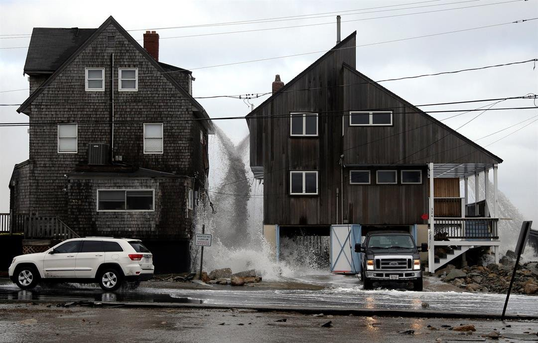 Ocean water pours off the roofs of these beachfront homes, as high surf continues in Marshfield, Mass. Utilities are racing to restore power to tens of thousands of customers in the Northeast still without electricity. (AP Photo/Elise Amendola)