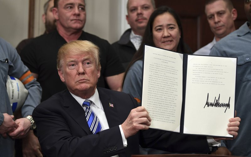 President Donald Trump holds up a proclamation on aluminum during an event in the Roosevelt Room of the White House in Washington, Thursday, March 8, 2018. He also signed one for steel.