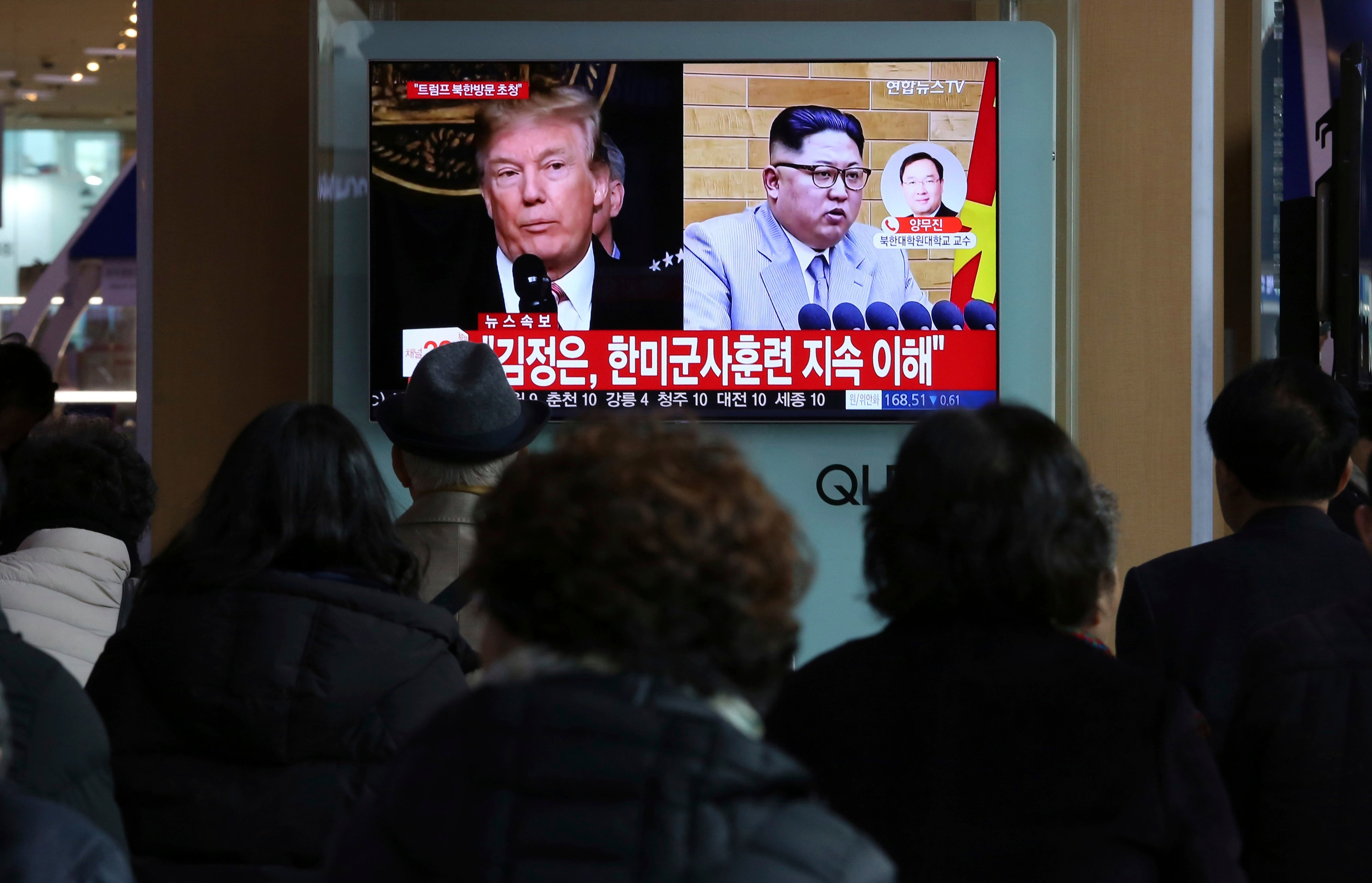 People watch a TV screen showing North Korean leader Kim Jong Un and U.S. President Donald Trump, left, at the Seoul Railway Station in Seoul, South Korea.