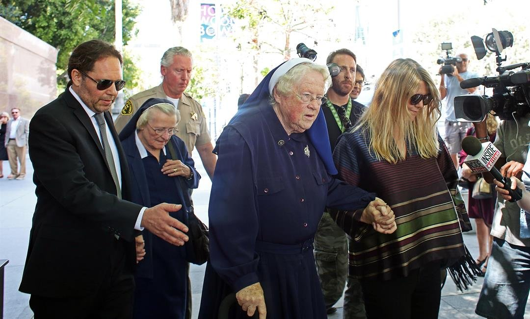Sisters Catherine Rose Holzman, second left, and Rita Callanan, center, is escorted by businesswoman Dana Hollister, right, out of Los Angeles Superior Court. (AP Photo/Anthony McCartney)