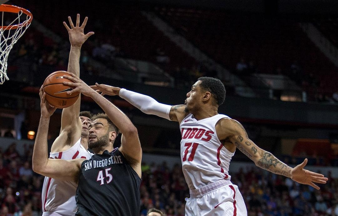 San Diego State center Kameron Rooks (45) pulls down a rebound next to New Mexico guard Troy Simons (31) during the first half of the championship of the MWC championship Saturday, March 10, 2018, in Las Vegas. (AP Photo/L.E. Baskow)