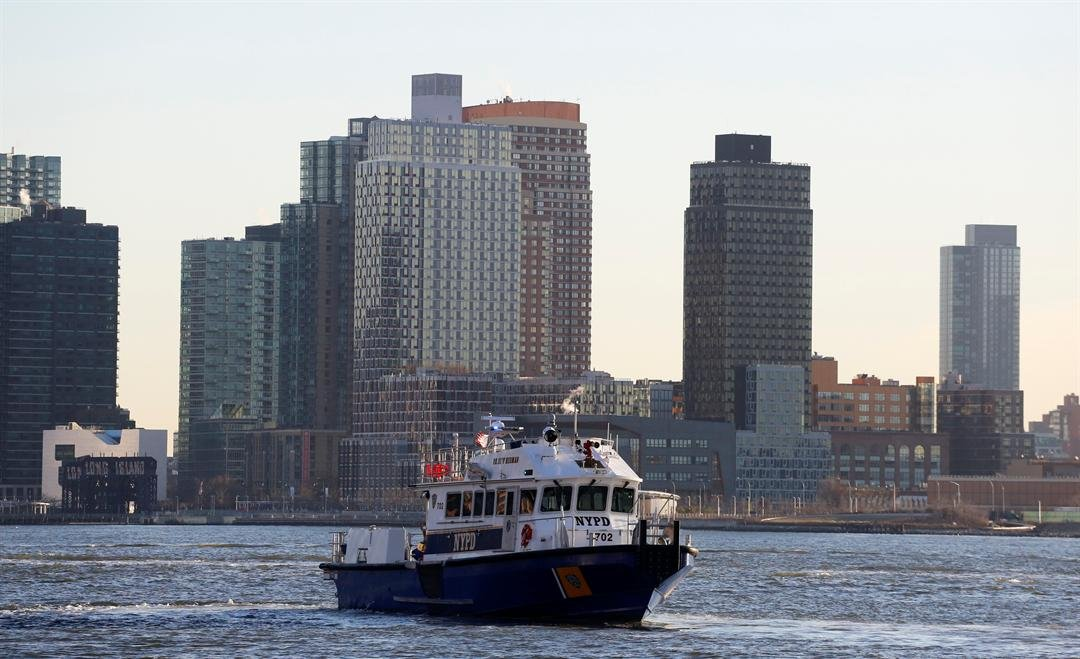 A police patrol boat is positioned near a sunken helicopter in the East River, Monday, March 12, 2018, in New York.
