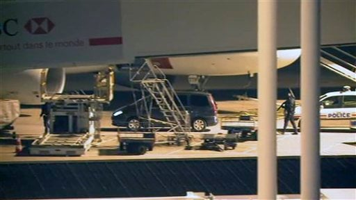 In this image from TV, showing tight security as a car carrying former Panamanian dictator, Manuel Noriega, approaches a plane at Orly airport, next to Paris, France, on Sunday, Dec.11, 2011. (AP)