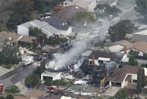 FILE - In this Dec. 8, 2008 file photo, smoke rises from a fire after an F-18 military jet crashed into a suburban neighborhood in San Diego.
