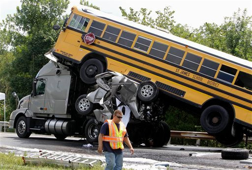 In this Aug. 5, 2010 file photo, a rescue worker is seen at the scene of an accident involving two school buses, a tractor-trailer and another passenger vehicle, near Gray Summit, Mo. (AP)