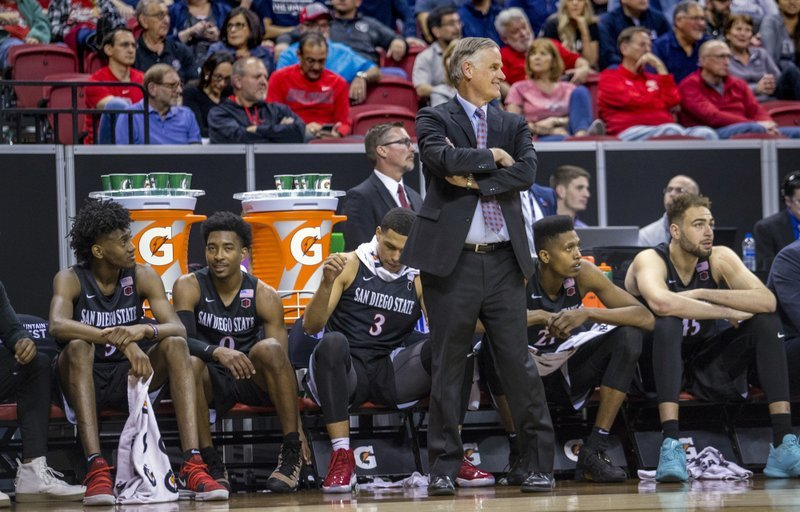 San Diego State head coach Brian Dutcher smiles during the second half of an NCAA college basketball game against Nevada in the semifinals of the Mountain West Conference tournament Friday, March 9, 2018, in Las Vegas.