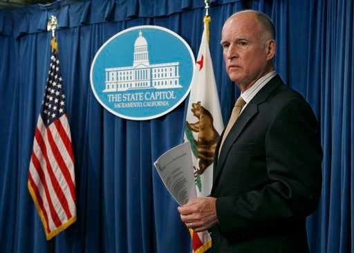 Gov. Jerry Brown listens to reporters ask Director of Finance Ana Matosantos questions about the state budget during a news conference at the Capitol in Sacramento, Calif., on Tuesday, Dec. 13, 2011. (AP Photo/Steve Yeater)