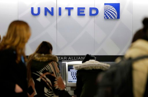 FILE- In this March 15, 2017, photo, people stand in line at a United Airlines counter at LaGuardia Airport in New York. (AP Photo/Seth Wenig, File)