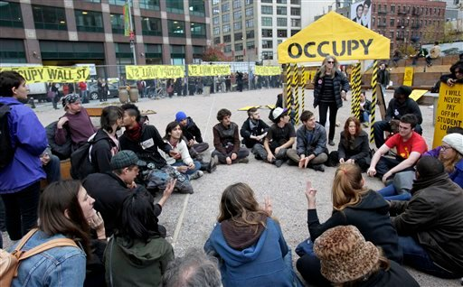 FILE - In this Nov. 15, 2011 photo, Occupy Wall Street protesters hold a general assembly meeting inside an enclosed site near Canal Street in New York. (AP Photo/Seth Wenig, File)