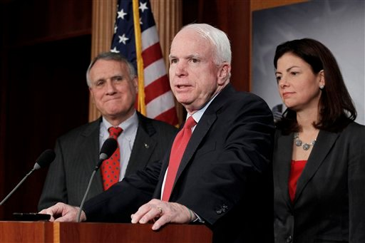 Sen. John McCain, R-Ariz., ranking Republican on the Senate Armed Services Committee, center, flanked by Senate Minority Whip Jon Kyl of Ariz., and fellow committee member Sen. Kelly Ayotte, R-N.H. (AP Photo/J. Scott Applewhite)