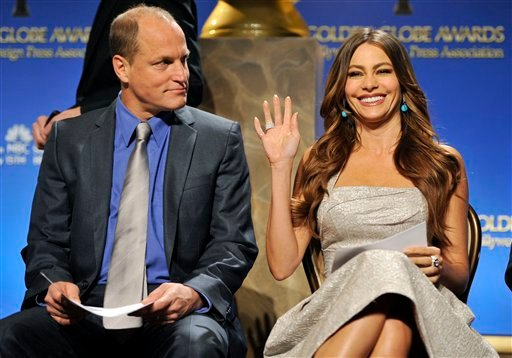 Presenter Sofia Vergara waves to photographers alongside fellow presenter Woody Harrelson before they announced nominations for the 69th Annual Golden Globe Awards, Thursday, Dec. 14, 2011, in Beverly Hills, Calif.