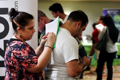 In this Jan. 30, 2018 photo, Loredana Gonzalez, of Doral, Fla., fills out a job application at a JobNewsUSA job fair in Miami Lakes, Fla.