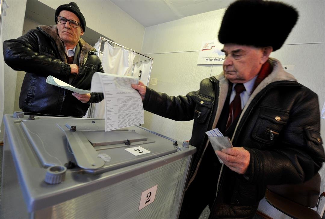 Two men cast their ballots at a polling station in Yelizovo, Petropavlovsk-Kamchatsky, Russian Far East, Russia. Polls have opened in Russia's Far East for the presidential election in which Vladimir Putin seeks a 4th term. (AP Photo/Alexander Petpov)