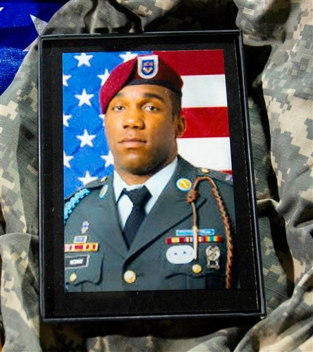 A photograph of Army paratrooper David Emanuel Hickman rests among memorabilia displayed during a candlelight vigil for the soldier killed in Baghdad last week, on Sunday, Nov. 20, 2011 at the highs school in McLeansville, N.C. (AP)