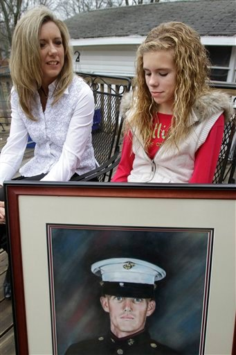 In this photo taken Dec. 14, 2011, in Decatur, Ill., Lexie Gifford, 12, right, reflects on the memories of her father, Marine Pvt. Jonathan Lee Gifford, portrait below, who was killed just two days into the Iraq war. (AP)