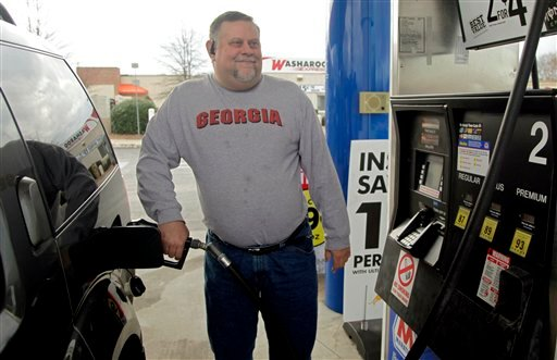 In this Dec. 15, 2011 photo, Michael Reed fills his gas tank at a station in Charlotte, N.C. (AP Photo/Chuck Burton)
