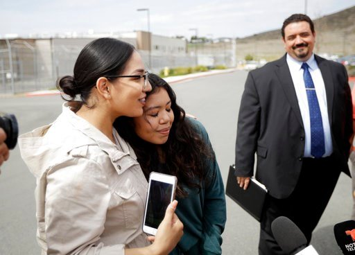 Chantal Estrada, center, a daughter of Perla Morales Luna, hugs family friend Judith Castro, left, as attorney Andres Moreno looks on, right, in front of the Otay Mesa Detention Center Tuesday, March 20, 2018, in San Diego.