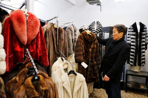 In this photo taken Friday, March 16, 2018, Benjamin Lin holds up a fur coat at the B.B. Hawk showroom in San Francisco. (AP Photo/Eric Risberg)