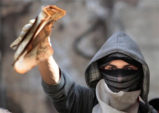 A masked Egyptian protester removes valuable books and documents from the two story building of the Egyptian Scientific Complex after it was almost gutted by fire which broke out during clashes with army soldiers last Saturday, near Tahrir Square (AP)