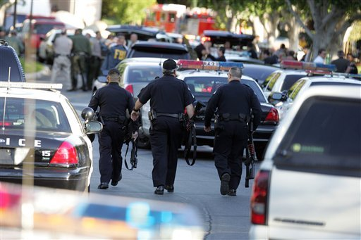 Police officers walk through the office building that houses offices of Southern California Edison after a man armed with a rifle shot two people, then shot himself in Irwindale, Calif., Friday, Dec. 16, 2011. (AP Photo/Ringo H.W. Chiu)
