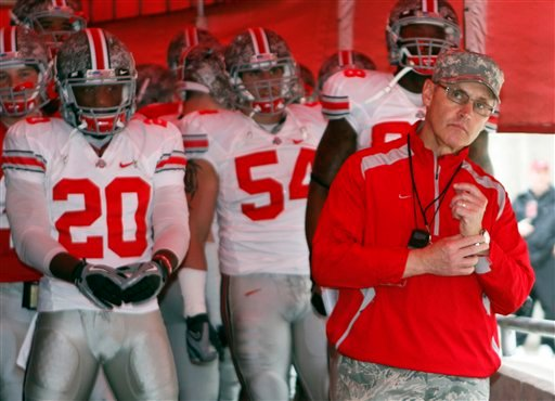 In this April 23, 2011, file photo, then-Ohio State head coach Jim Tressel, right, looks out on the field as he stands with his team before an NCAA college football Spring Game in Columbus, Ohio.