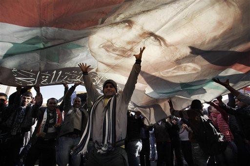 A Syrian man gestures under a large poster depicting Syria's President Bashar Assad during a rally in Damascus, Syria, Monday, Dec. 19, 2011. (AP Photo/Muzaffar Salman)