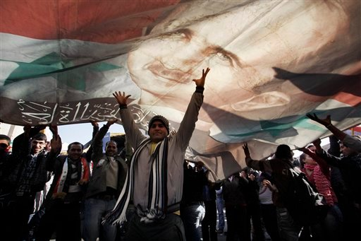A Syrian man gestures under a large poster depicting Syria's President Bashar Assad during a rally in Damascus, Syria, Monday, Dec. 19, 2011. (AP Photo/Muzaffar Salman)