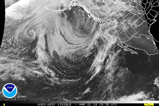 "This March 21, 2018 satellite image provided by the NOAA shows a strong Pacific storm, known as a ""Pineapple Express,"" the lower arc of clouds that range from Hawaii at lower left, aimed directly at California, middle right, that dropped heavy rain on a w"