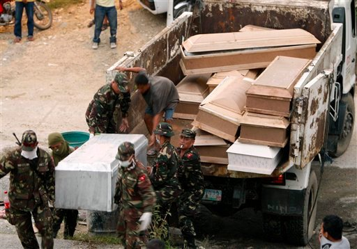 Soldiers carry coffins of flash flood victims during a mass burial Tuesday Dec. 20, 2011 at a public cemetery in Iligan city in southern Philippines.