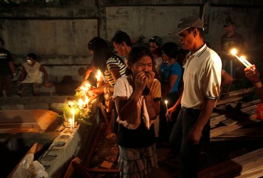 A relative weeps during mass burial for victims of Friday's flash flooding Tuesday Dec. 20, 2011 at a public cemetery in Iligan city in southern Philippines.