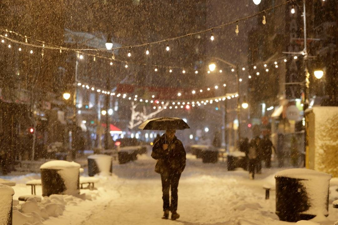A person holds an umbrella while walking in downtown Jersey City, N.J., during a snowstorm. A spring nor'easter targeted the Northeast on Wednesday with strong winds and a foot or more of snow expected in some parts of the region. (AP Photo/Julio Cortez)