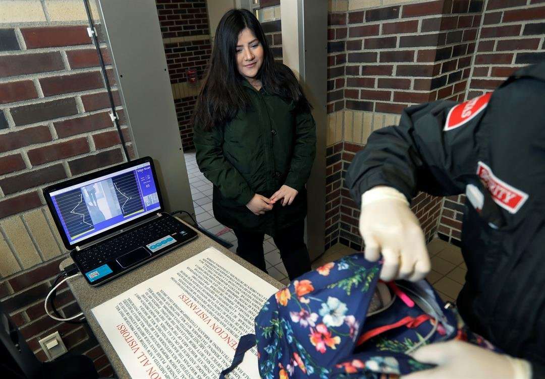 In a photo from Thursday, March 8, 2018, in Detroit, Alondra Alvarez, a student at Western International High School, goes through a metal detector.