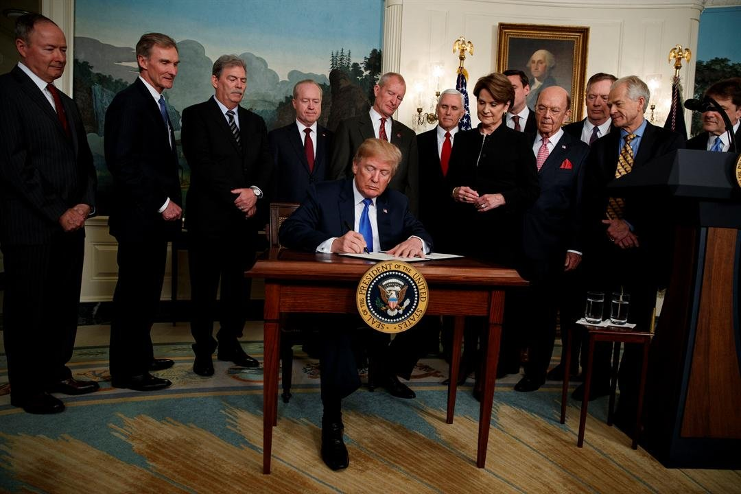 President Donald Trump signs a Presidential Memorandum imposing tariffs and investment restrictions on China, in the Diplomatic Reception Room of the White House, Thursday, March 22, 2018, in Washington. (AP Photo/Evan Vucci)