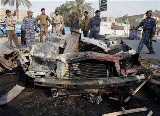 Iraqi security forces and people gather the scene of a car bomb attack in Baghdad, Iraq, Thursday, Dec. 22, 2011.  (AP Photo/Karim Kadim)