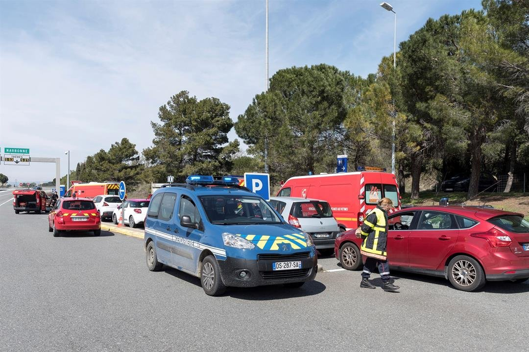 French police and firefighters secure the entrance of Trebes, southern France, where an armed man took hostages in a supermarket, Friday, March 23, 2018. French national police say two people have been killed and about a dozen wounded.(AP Photo/Jean-Paul)