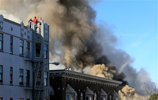 A group of people look on at an apartment fire in the Western Addition area of San Francisco, Thursday, Dec. 22, 2011. (AP Photo/Jeff Chiu)