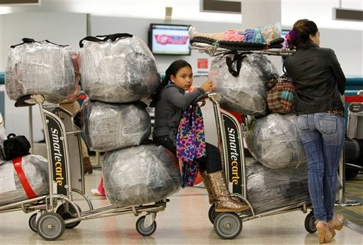 Liedy Hernandez of Miami waits in line with luggage at Miami International Airport before traveling to Cuba with her family, Monday, Dec. 19, 2011, in Miami. (AP Photo/Lynne Sladky)