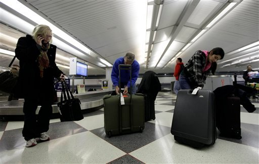 Travelers check their luggage at an United Airlines baggage claim area at O'Hare International Airport in Chicago, Thursday, Dec. 22, 2011. Snow and rain expected to cause holiday travel delays. (AP Photo/Nam Y. Huh)