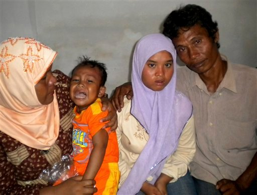 15-year-old Wati, second right, poses for a photograph with her father Yusuf, right, mother Yusniar, left, and younger brother Aris at their home in Meulaboh, Aceh province, Indonesia Dec. 23, 2011. (AP Photo)